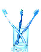 Toothbrush in glass and chewing gum on blue background — Stock Photo