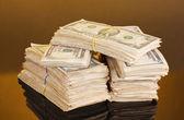 Stacks of dollars on orange background — Stock Photo