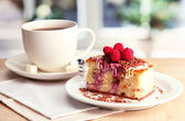 Sweet cake with cup of tea on wooden table — Stock Photo