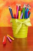 Colorful pencils and felt-tip pens in green pail on color background — Stock Photo