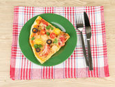 Plate with a slice of delicious pizza on wooden background — Stock Photo