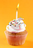 Tasty birthday cupcake with candle, on orange background — Stock Photo