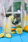 Citrus lemonade in pitcher and glass of citrus around on blue wooden table — Stock Photo