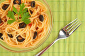 Italian spaghetti in glass bowl on bamboo mat close-up — Stock Photo