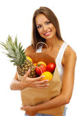 Beautiful young woman with fruits in shopping paper bag, isolated on white — Stock Photo