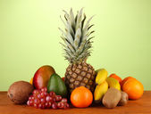 Still life of fruit on a table on a green background — Stock Photo