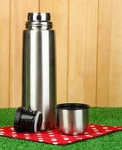 Metal thermos on grass on wooden background — Stock Photo