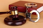 Gavel, handcuffs and book on law on beige background — Stock Photo