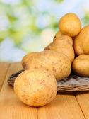 Batatas maduras no berço de vime na mesa de madeira no fundo natural fechar- — Fotografia Stock