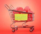 Shopping trolley with jelly candies, on red background — Stock Photo