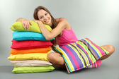 Beautiful young girl with pillows on grey background — Stock Photo