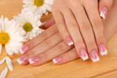 Woman hands with french manicure and flowers on wooden background — Stock Photo