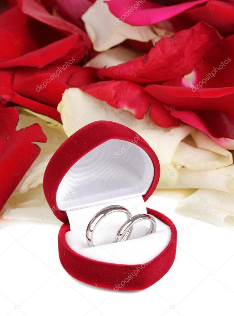 Belle boîte avec anneaux de mariage sur les pétales de roses rouges ...