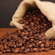 Coffee beans in bag on table on dark background — Stock Photo #13778089