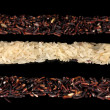 Three strips of black and white rice isolated on black - Stock Photo