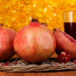Ripe pomegranates on wicker cradle with glass of pomegranate juice on woode - Stock Photo