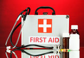 First aid box, on red background — Stockfoto