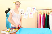 Beautiful young dressmaker in workroom — Stock Photo