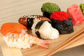 Delicious sushi served on wooden board on bamboo mat close-up — Stock Photo