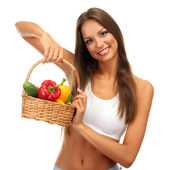 Beautiful young woman with vegetables in basket, isolated on white — Stock Photo