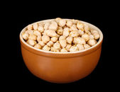 White chickpeas in brown bowl isolated on black — Stock Photo