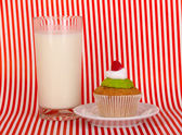 Glass of fresh new milk with cake on red striped background — Stock Photo