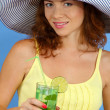Smiling beautiful girl with beach hat and cocktail on blue background - Stock Photo
