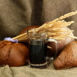 Tankard of kvass and rye breads with ears, on burlap background — Stock Photo #13780075