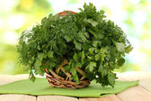 Wooden basket with parsley and dill on wooden table on natural background — Stock Photo