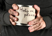 Homeless man asks for help, on black background close-up — Stock Photo