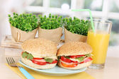 Appetizing sandwiches on color plate on wooden table on window background — Stock Photo