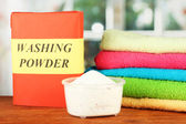 Box of washing powder with blue measuring cup and towels, on wooden table c — Stock Photo