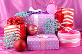 Colorful purple, red and pink gifts with Christmas balls and snowflakes on — Stock Photo