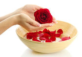 Woman hands with wooden bowl of water with petals, isolated on white — Stock Photo
