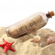 Glass bottle with note inside on sand isolated on white — Stock Photo