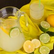 Citrus lemonade in glass and pitcher of citrus around on yellow fabric on w — Stockfoto