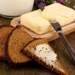 Butter on wooden holder surrounded by bread and milk on wooden table close- — Stock Photo