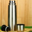 Metal thermos on grass on wooden background — Stock Photo #13802385