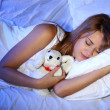 Young beautiful woman with toy rabbit sleeping on bed in bedroom — Stock Photo