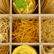 Nine types of pasta in wooden box sections close-up — Stock Photo