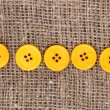 Stock Photo: Colorful sewing buttons on sackcloth