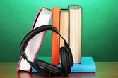 Casque avec des livres sur la table en bois sur fond turquoise — Photo