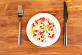 A lot of pills in a plate with knife and fork on wooden background close-up — Stock Photo