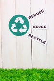 Recycling sign on wooden background — Stock Photo