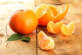 Ripe tasty tangerines on wooden background — Stock Photo