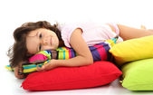 Beautiful little girlwith pillows isolated on white — Stock Photo