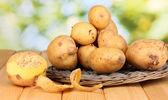 Batatas maduras no berço de vime na mesa de madeira no fundo natural — Fotografia Stock