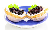 Sweet cakes with berries on saucer isolated on white — Stock Photo