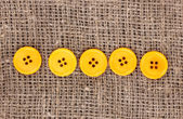 Colorful sewing buttons on sackcloth — Stock Photo