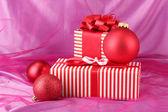 Regali rossi colorati con fiocco e natale palle su sfondo rosa — Foto Stock